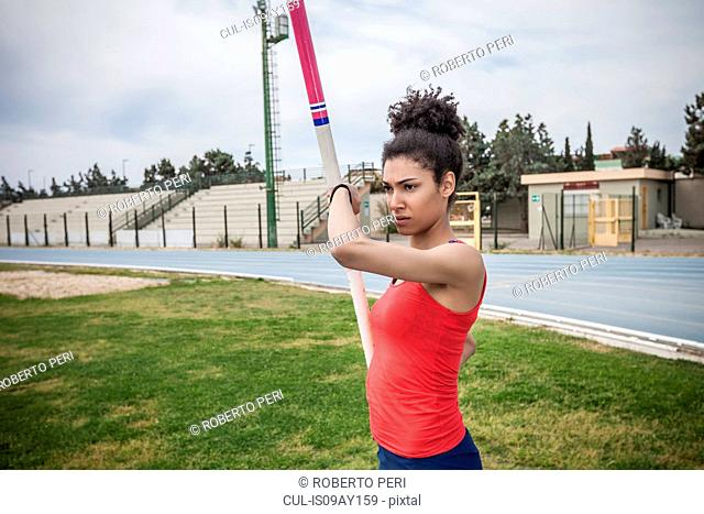 Young female pole vaulter concentrating at sport facility