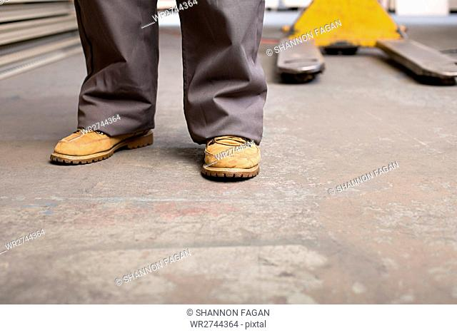 Feet and legs of a person in warehouse