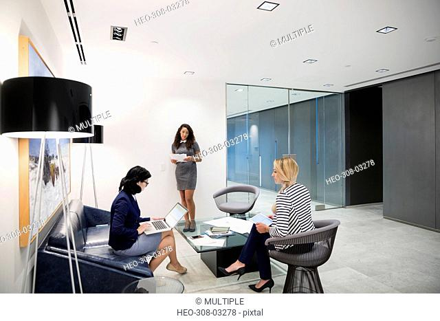 Businesswoman using laptop and digital tablet in office lobby
