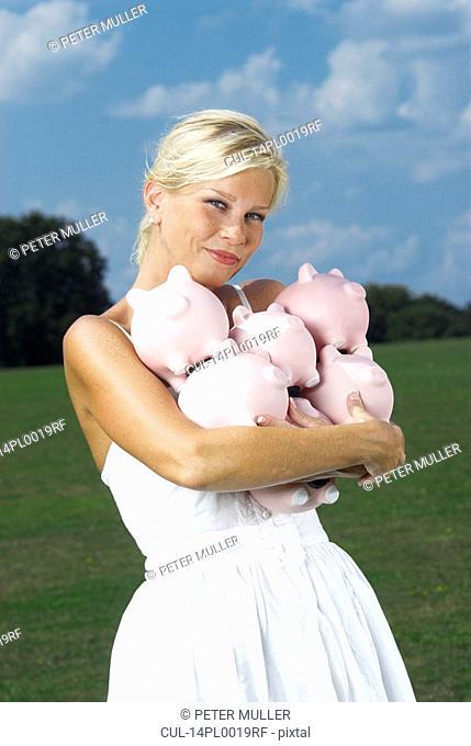 woman holding piggy banks