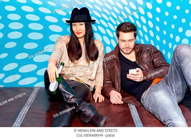 Couple sitting on floor, holding bottle of beer and smartphone