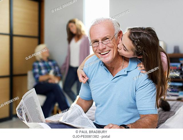 Girl kissing grandfather in home
