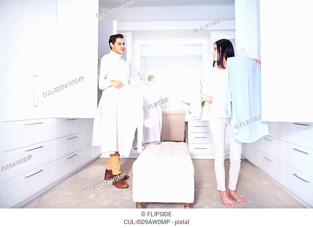 Young couple making decisions whilst getting ready in bedroom