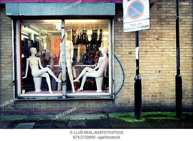 A shop window with three naked female mannequins. East End, London, England