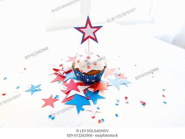 independence day, celebration, patriotism and holidays concept - close up of glazed cupcake or muffin decorated with star and cofetti on table at 4th july party