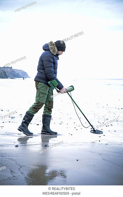 Man with metal detector at the sand beach