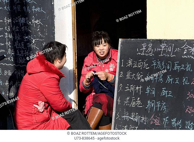 women next to their office in a small street in Nanjing, China