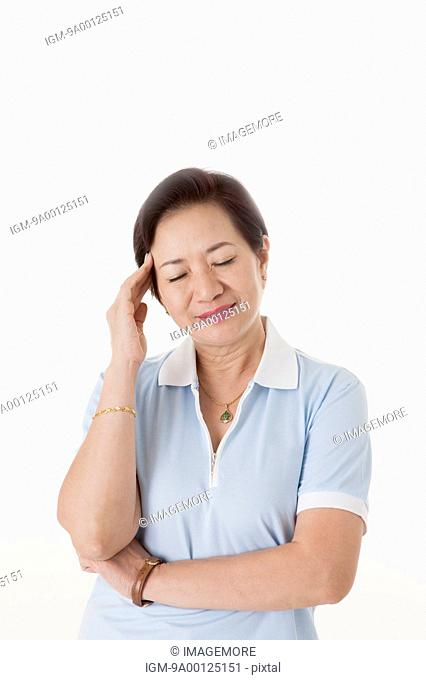 Senior woman closing eyes with hand on head