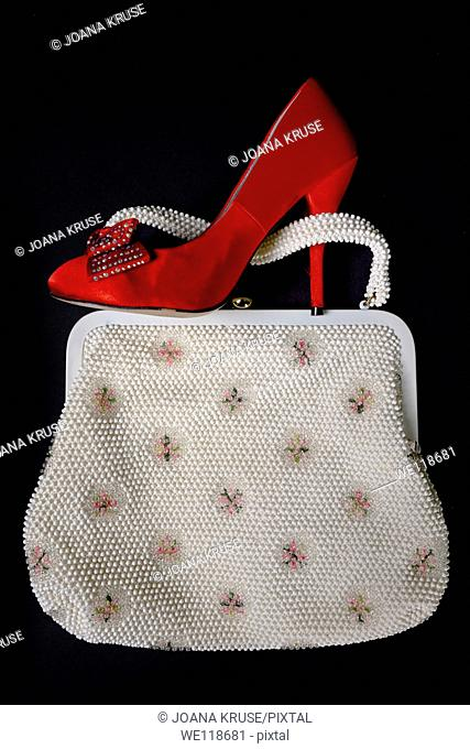 a red shoe with high heels on a vintage handbag