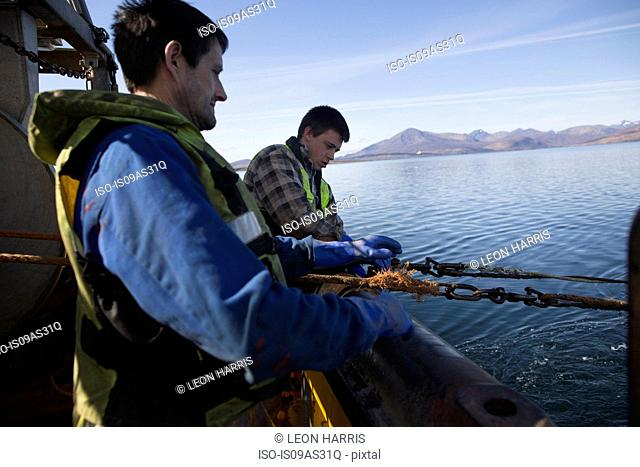 Fisherman releasing net into sea, Isle of Skye, Scotland