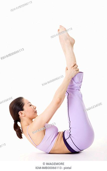 Woman practicing yoga with legs in the air