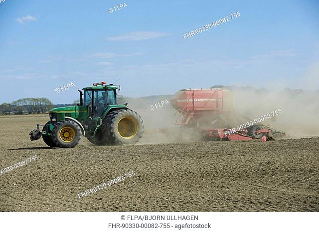 John Deere 7800 tractor with Horsch seed drill, drilling in dusty arable field, Sweden, April