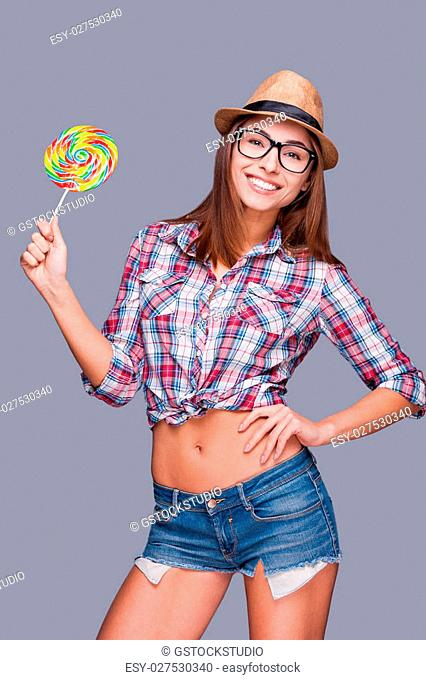 Joyful lollipop. Beautiful young woman in funky hat holding a big lollipop and smiling while standing against grey background