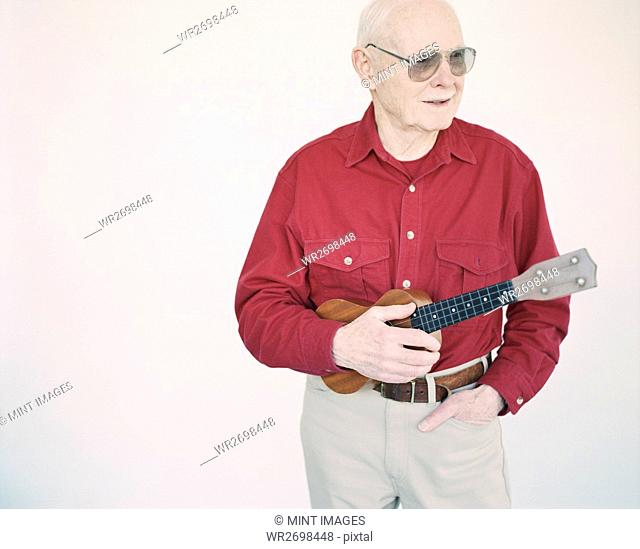 An elderly man in a red shirt holding a ukulele