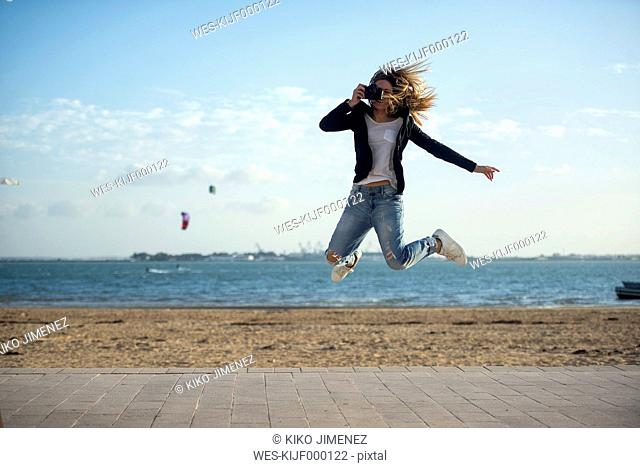 Spain, Puerto Real, woman taking a picture while jumping in the air