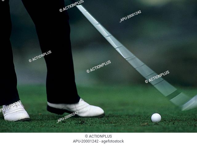 Action shot of a golfer striking a ball