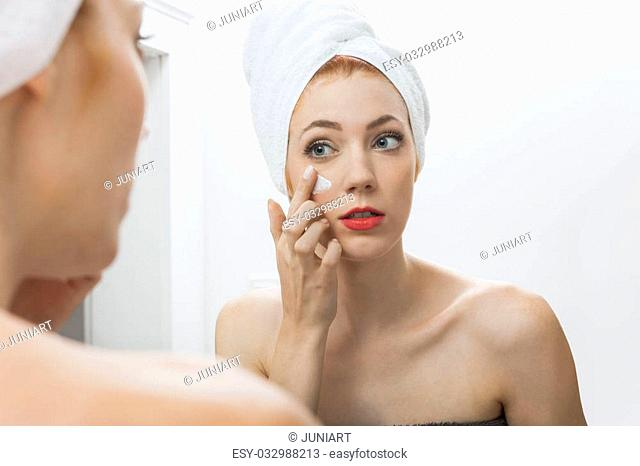Close up Fresh Woman After Shower Applying White Cream on her Face in Front a Mirror With Towel on her Head