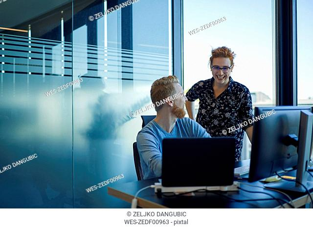 Two happy colleagues at desk in office