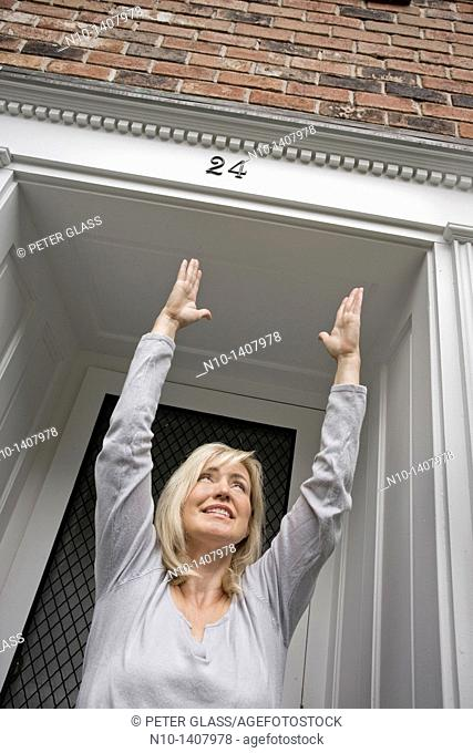 Middle-age blond woman standing by her front door