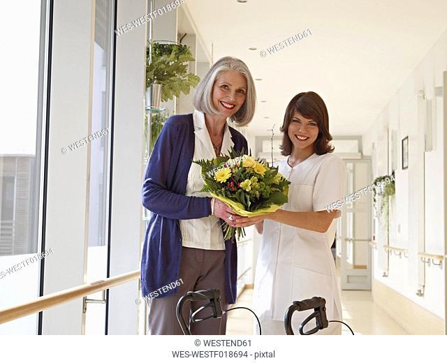 Germany, Cologne, Senior women and caretaker holding bouquet in corridor of nursing room, smiling, portrait