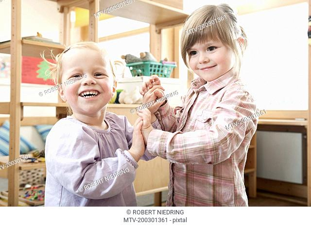 Two smiling little girls holding hands in kindergarten