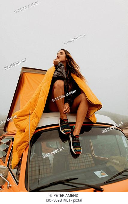 Young woman looking out from top of recreational vehicle at beach, Jalama, California, USA