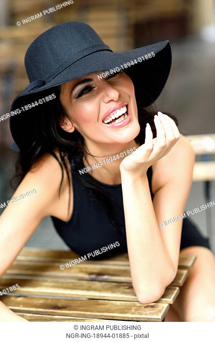 Brunette woman wearing black seductive dress and sun hat laughing in a bar in the street. Young girl with curly hairstyle in urban background