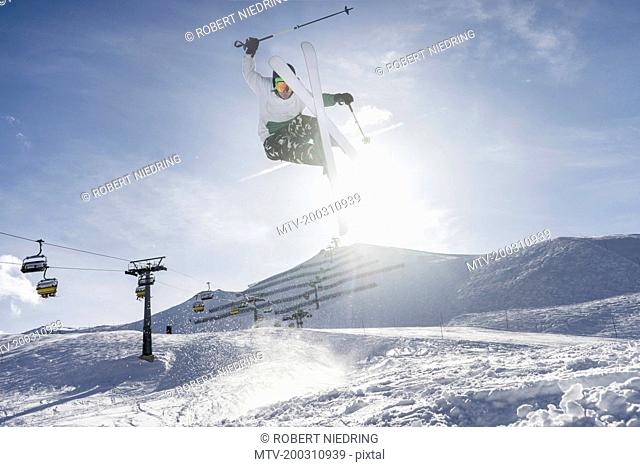 Skier jumping on snowcapped mountain