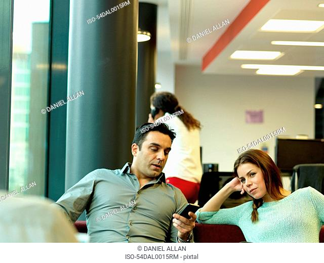 Business people relaxing in office lobby