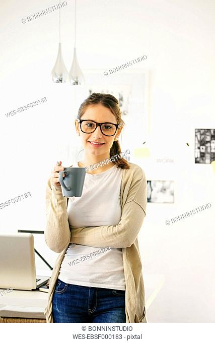 Portrait of woman with coffee cup at modern home office