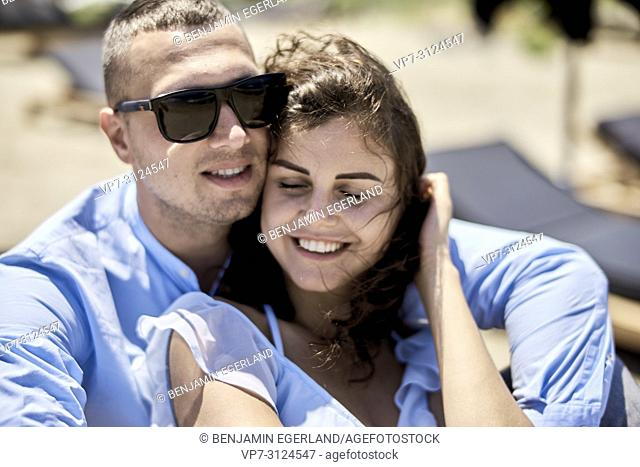 man embracing woman, on sunbeds, vacations, love, affair, sensual, couple, flirt, summer0