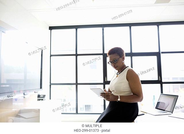 Businesswoman using digital tablet in conference room