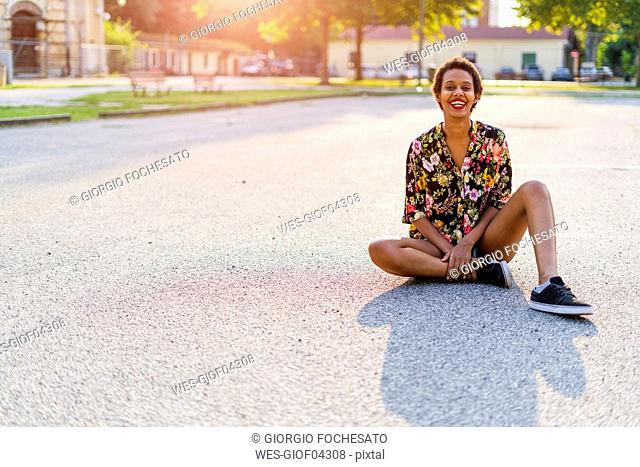 Portrait of laughing young woman sitting outdoors at sunset