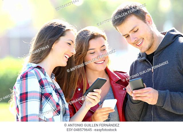 Three happy teen friends sharing smart phone content outdoors