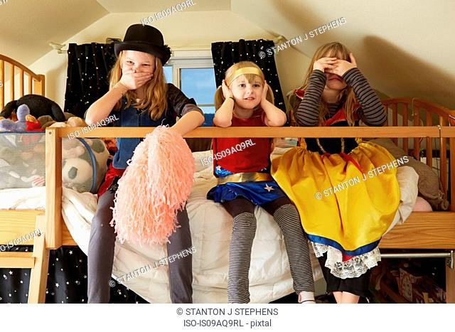 Three sisters, sitting on bed, wearing fancy dress costumes, covering mouth, ears and eyes