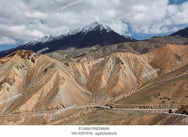 Trucks travel along the Srinagar-Leh Highway in the remote area of Fotula, Ladakh, India. The mountainous landscape is typical of the Trans-Himalayan high...