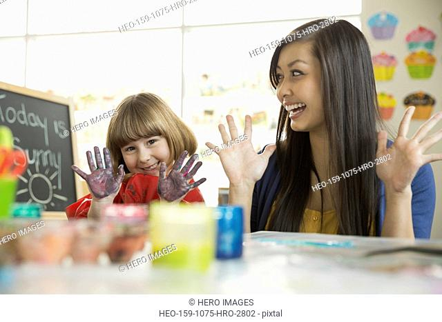 Teacher with girl finger painting in art class