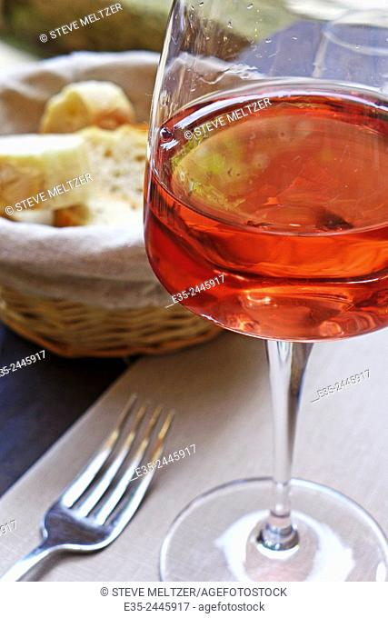 A glass of wine and a basket of bread