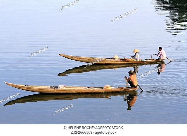 Fishermen on Hue river in traditional wooden canoe, Hue, Vietnam, Asia