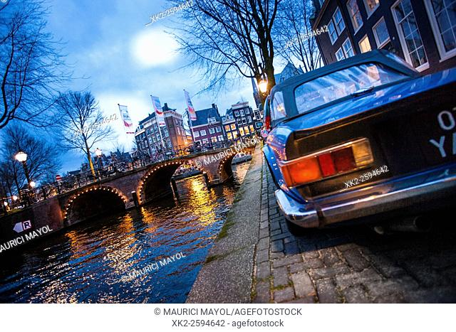 Blue car parked in Leidsegracht looking at Herengracht bridge, Amsterdam, Holland