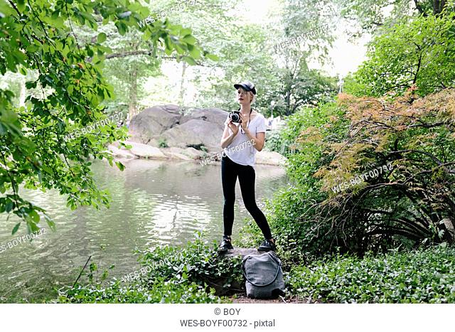 Young woman with a vintage camera taking pictures in park