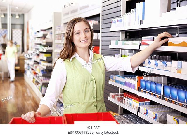 Young femail pharmacist looking for medicine in drugstore