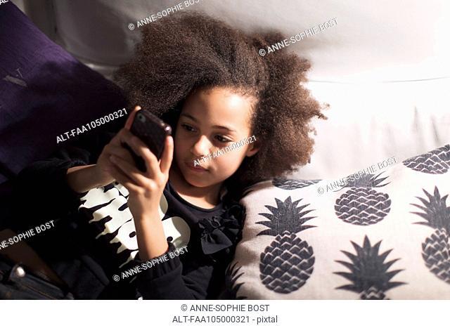 Girl lying down, using smartphone