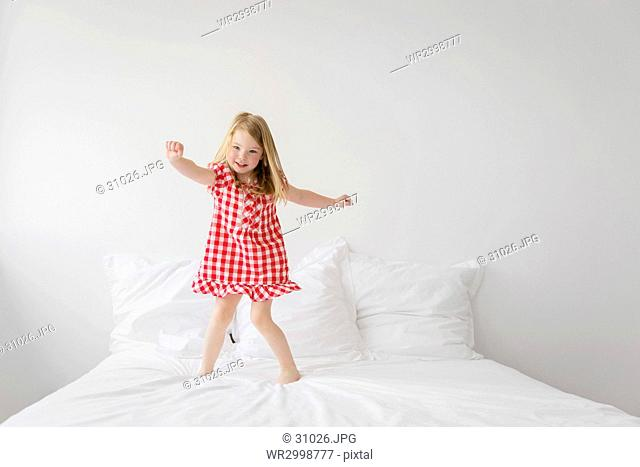 Smiling blond girl wearing red and white checkered dress jumping on bed with white duvet