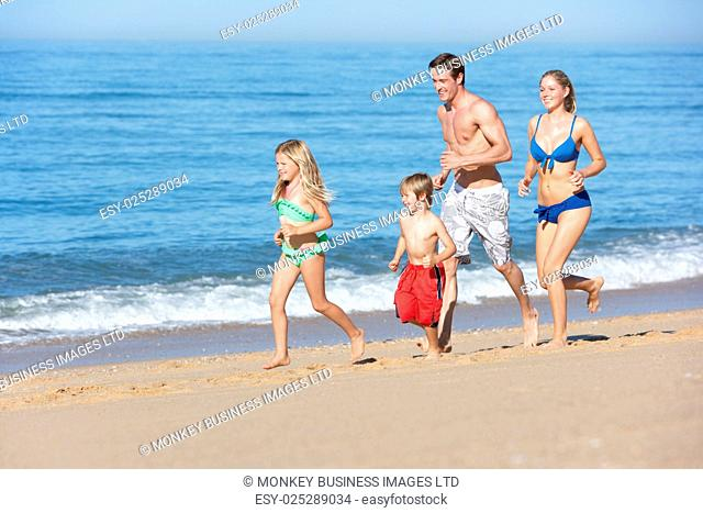 Family Enjoying Beach Holiday Running Along Beach