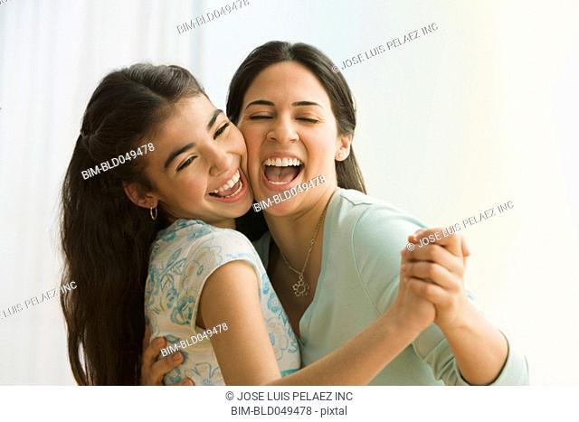 Hispanic mother and daughter dancing