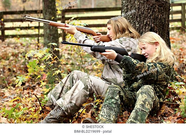 Mother and daughter in camouflage aiming rifles in forest