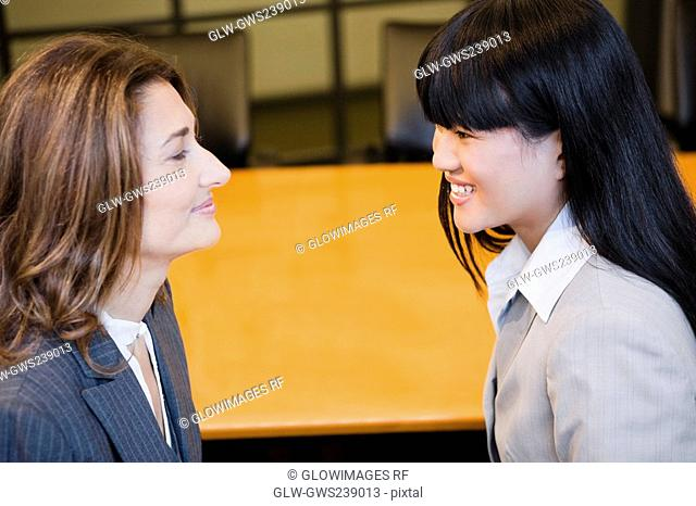 Close-up of two businesswomen smiling