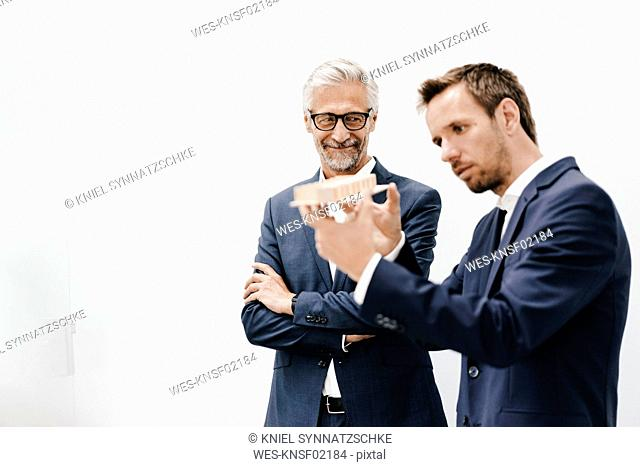 Two businessmen examining architectural model
