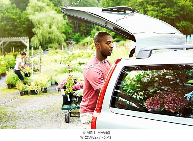 Car parked at a garden centre, man loading flowers into the boot
